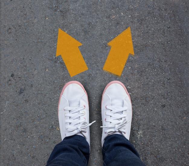 Para buty stoi na asfaltowej drodze z dwa strzała Premium Zdjęcia