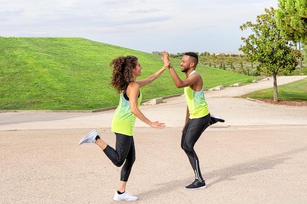 Para czarnoskórych i białych kobiet jest szczęśliwa uprawiając sport i biegając, witają się rękami, są w parku ubrani w odzież sportową Premium Zdjęcia