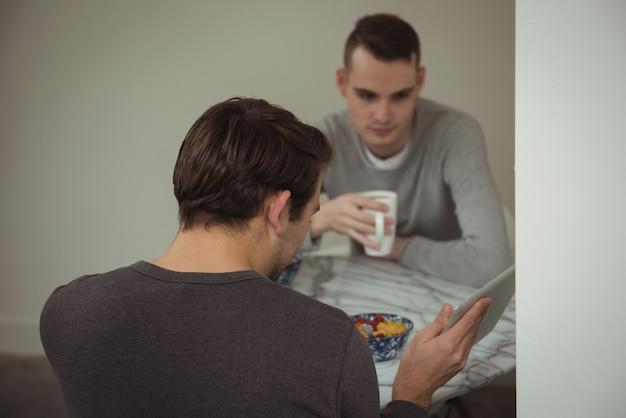 Para Gejów, Patrząc Na Cyfrowy Tablet Jedząc śniadanie Darmowe Zdjęcia
