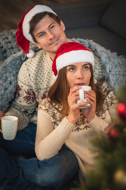 Para jest ubranym santa kapelusze z gorącymi napojami Darmowe Zdjęcia