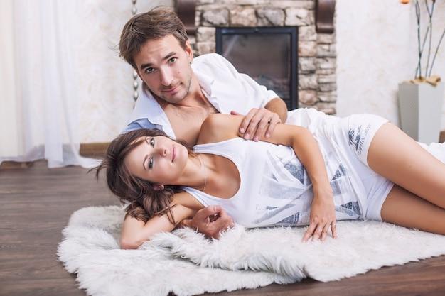 Para Mężczyzna I Kobieta Przytulanie W Domu, Leżąc Na Dywanie Premium Zdjęcia