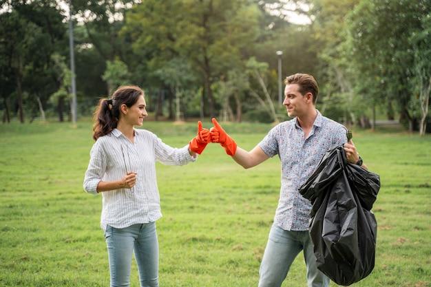Para Miłośników Wolontariuszy W Rękawiczkach Idzie Do Zbierania śmieci W Parku Aby Utrzymać środowisko W Czystości Premium Zdjęcia
