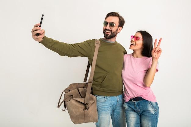 Para Na Białym Tle, Dość Uśmiechnięta Kobieta W Różowej Koszulce I Mężczyzna W Bluzie Z Torbą Podróżną, W Dżinsach I Okularach Przeciwsłonecznych, Dobrze Się Bawią, Podróżują Razem Robiąc śmieszne Selfie Zdjęcie Na Telefon Darmowe Zdjęcia