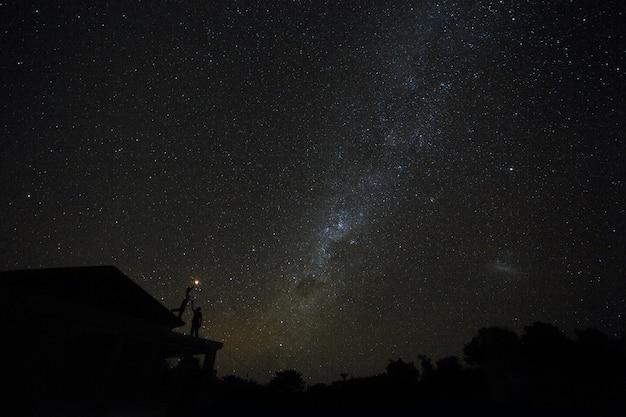 Para na dachu ogląda tajemniczy sposób i gwiazdy na nocnym niebie na wyspie bali. Premium Zdjęcia