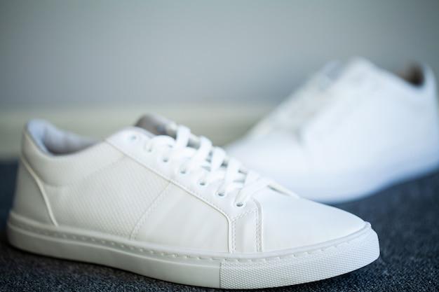 Para nowych stylowych białych tenisówek na podłodze w domu Premium Zdjęcia