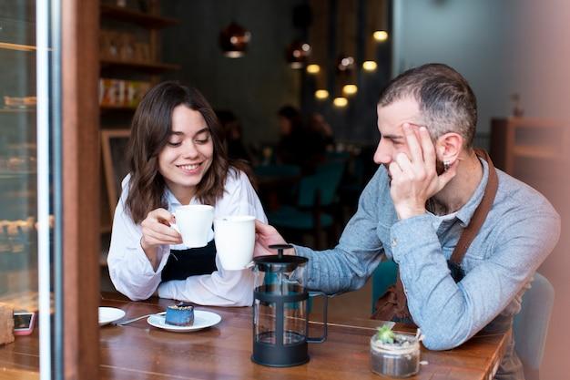 Para pracuje przy sklep z kawą i pije kawę Darmowe Zdjęcia