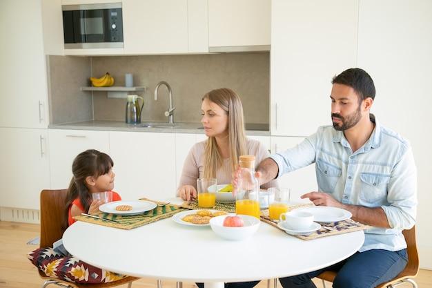 Para Rodziców I Dziewczynka Jedzą śniadanie, Siedzą Przy Stole Z Owocami, Ciastkami I Sokiem Pomarańczowym, Rozmawiają I Jedzą. Darmowe Zdjęcia
