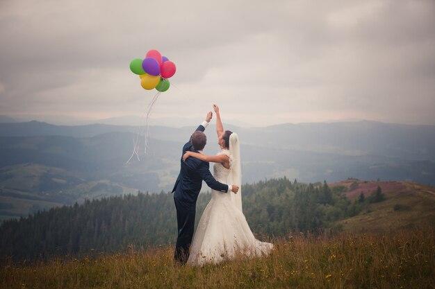 Para ślub Przytulanie I Wystrzeliwanie Kolorowych Balonów W Niebo Premium Zdjęcia