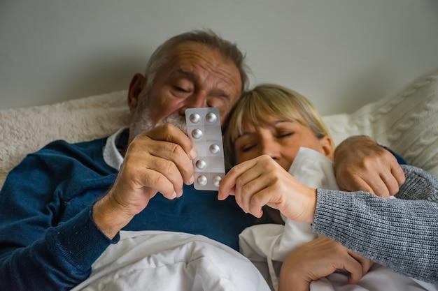 Para Starszych Na łóżku I Ręce Trzymając Leki Premium Zdjęcia