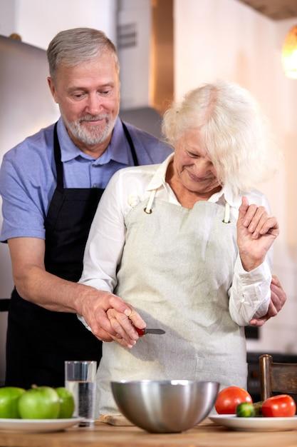 Para Starszych Przygotowuje Sałatkę Warzywną W Kuchni, Siwy Przystojny Mężczyzna Pomaga żonie W Gotowaniu, Jadąc Zdrowe śniadanie Premium Zdjęcia