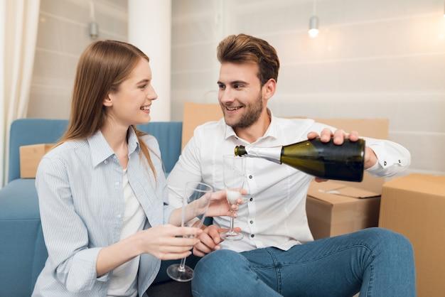 Para świętuje z szampanem przeprowadzka do nowego mieszkania. Premium Zdjęcia