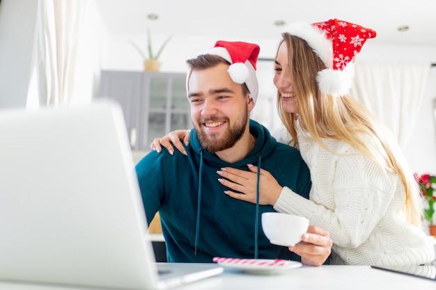 Para szuka czegoś w komputerze na święta bożego narodzenia Premium Zdjęcia