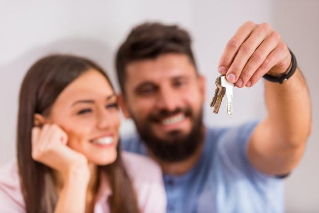 Para trzymając klucze do nowego domu, przeprowadzka do nowego domu. Premium Zdjęcia
