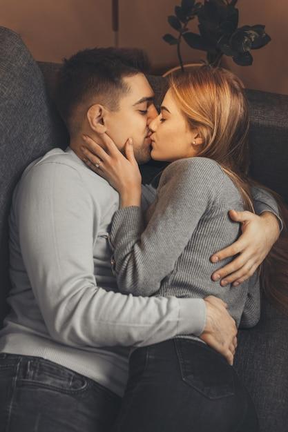 Para W Szarych Swetrach Leży Na Sofie I Obejmuje Się Podczas Namiętnych Pocałunków Premium Zdjęcia