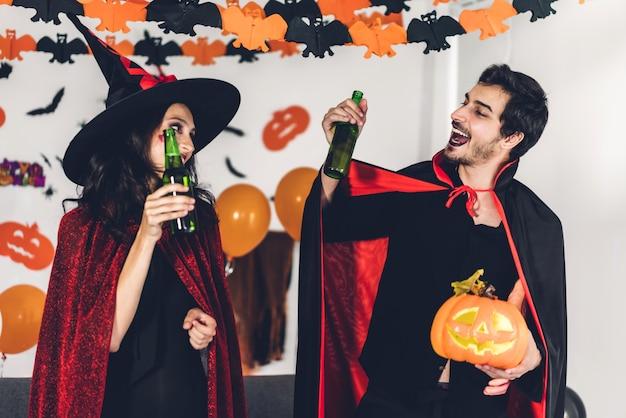 Para Zabawy Trzymając Dynie I Noszenie Ubranych Karnawałowych Kostiumów Na Halloween Premium Zdjęcia