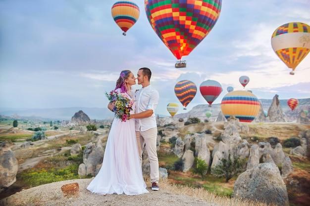 Para Zakochanych Stoi Na Tle Balonów W Kapadocji. Mężczyzna I Kobieta Na Wzgórzu Patrzą Na Dużą Liczbę Latających Balonów. Turcja Kapadocja Bajkowa Sceneria Gór. ślub Na Naturze Premium Zdjęcia