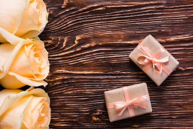 Para zawijająca prezent i rosebuds na drewnie, odgórny widok Premium Zdjęcia