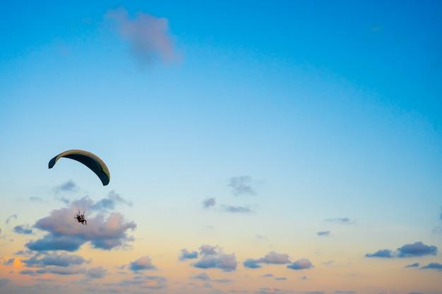 Paralotnia latająca na niebie o zachodzie słońca Premium Zdjęcia