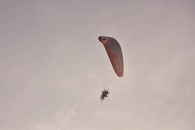 Paramotor (powered paraglider) z czerwono-białym spadochronowym lataniem w niebie, sport ekstremalny. Premium Zdjęcia