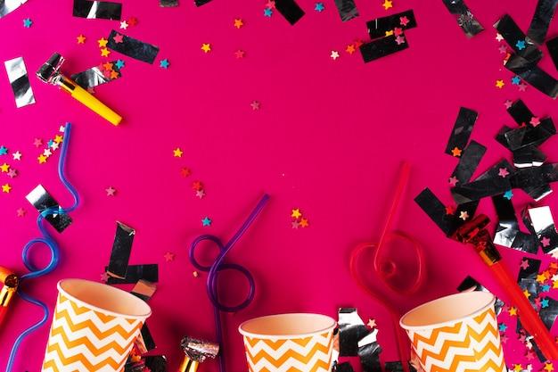 Partyjny świecidełko I Kolorowe Filiżanki Zamykamy Up Na Purpurowym Tle Premium Zdjęcia