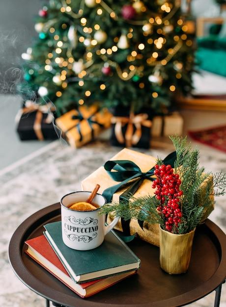 Paruj Nad Filiżanką Gorącej Herbaty Z Cytrynowo-cynamonowym świątecznym Wystrojem I Eleganckim Drzewkiem W Bokeh Premium Zdjęcia