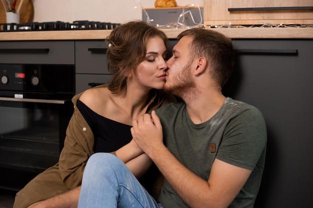 Pary Całowanie W Kuchennym Obsiadaniu Na Podłoga Premium Zdjęcia