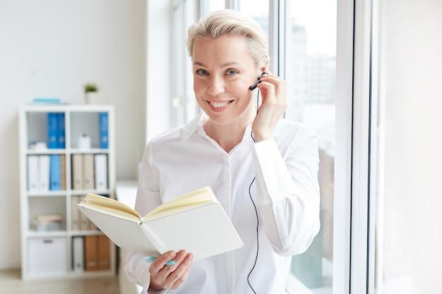 Pasa W Górę Portret Uśmiechnięta Bizneswoman Noszenie Zestawu Słuchawkowego I Patrząc Podczas Pracy W Call Center Premium Zdjęcia