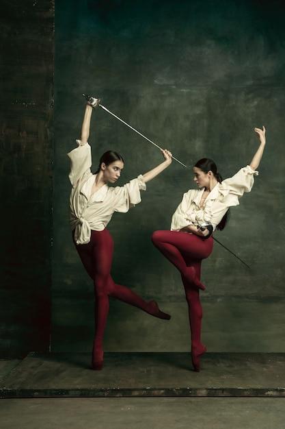 Pasja. Dwie Młode Tancerki Baletowe Lubią Pojedynki Z Mieczami Na Ciemnozielonej ścianie. Kaukaskie Modele Tańczą Razem. Koncepcja Baletu I Współczesnej Choreografii. Darmowe Zdjęcia