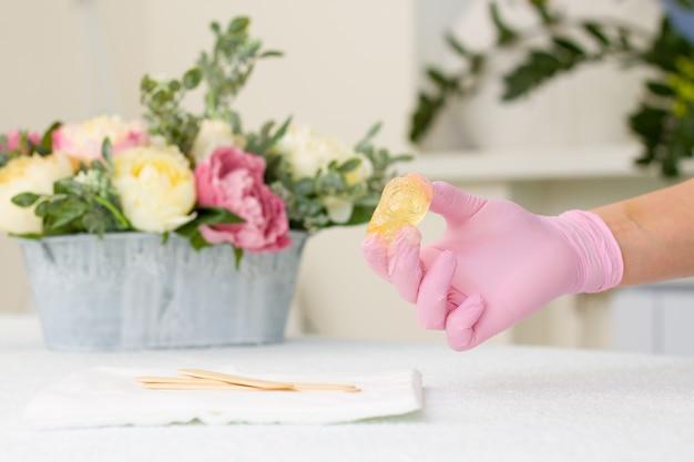 Pasta cukrowa lub miód woskowy do usuwania włosów za pomocą różowych rękawiczek rąk kosmetologa w salonie spa Premium Zdjęcia