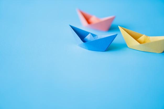 Pastelowa koloru papieru łódź na czystym tle z kopii przestrzenią Premium Zdjęcia