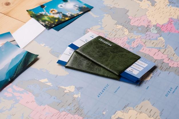Paszporty I Bilety Umieszczone Na Papierowej Mapie świata Z Malowniczymi Zdjęciami Premium Zdjęcia