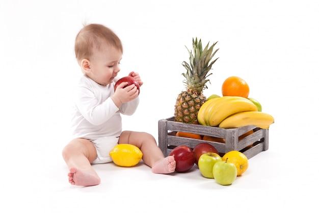 Patrzeć owocowego ślicznego uśmiechniętego dziecka na bielu wśród fru Premium Zdjęcia