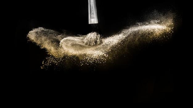 Pędzel kosmetyczny ze złotym kosmetykiem w proszku do makijażu Premium Zdjęcia