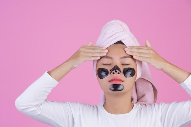 Peeling kosmetyczny. młoda suczka z czarną maską peel off na skórze kosmetyk złuszczający produkt do twarzy na różowo Darmowe Zdjęcia