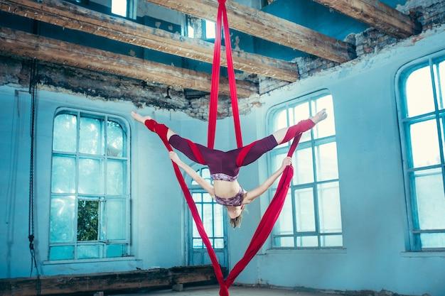 Pełen Wdzięku Gimnastyczka Wykonujący ćwiczenia Lotnicze Z Czerwonymi Tkaninami Na Niebieskim Tle Starego Poddasza. Młoda Nastolatka Kaukaski Pasuje. Darmowe Zdjęcia