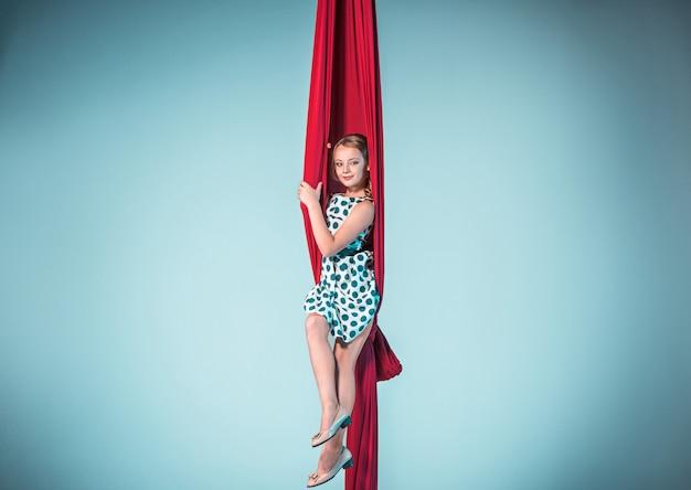 Pełen Wdzięku Gimnastyk Siedzący Z Czerwonymi Materiałami Darmowe Zdjęcia