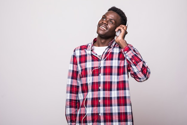 Pełna Długość Portret Młodego Mężczyzny Afro American Słuchanie Muzyki W Słuchawkach Na Białym Tle Darmowe Zdjęcia