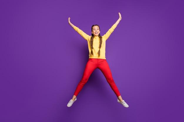 Pełne Ciało Szalona Młoda Dama Skacząca Wysoko Spędzająca Wolny Czas Rozkładaj Ręce W Kształcie Gwiazdy Nosić Swobodny żółty Sweter Czerwone Spodnie Izolowane Fioletowa ściana Premium Zdjęcia