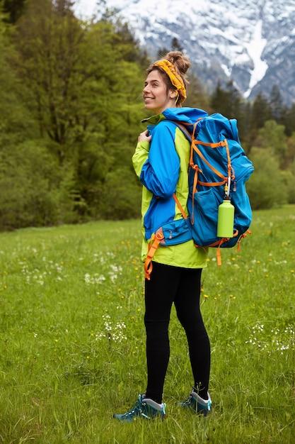Pełne Ujęcie W Pionie Przedstawiające Zadowoloną Aktywną Turystkę Ubraną W Strój Sportowy, Wędrującą Po Zielonej łące Darmowe Zdjęcia