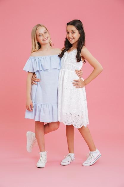 Pełne Zdjęcie Księżniczek Dziewcząt Ubranych W Sukienki, Uśmiechając Się I Patrząc Na Kamery, Przytulając Się Razem, Odizolowane Na Różowym Tle Premium Zdjęcia