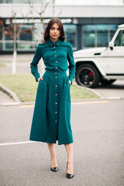 Pełne Zdjęcie Pięknej Kobiety W Zielonej Sukience Stojącej Na Zewnątrz Podczas Pozowania Do Kamery. Koncepcja Stylu I Mody Darmowe Zdjęcia