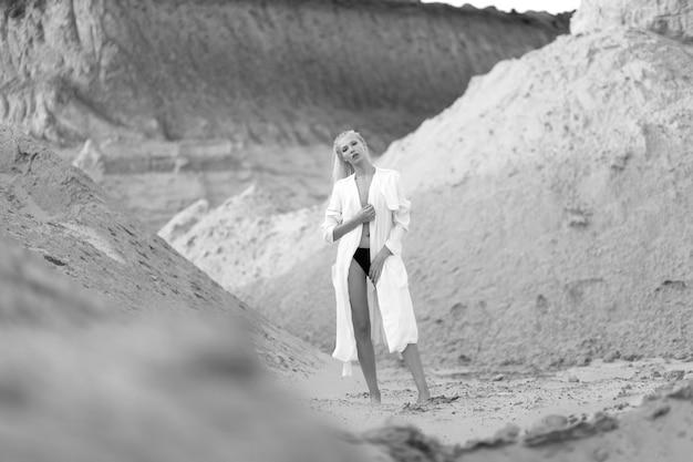 Pełnej Długości Portret Kaukaskiej Modelki O Blond Włosach W Białej Długiej Koszuli Z Boso Na środku Pustyni Piasku. Premium Zdjęcia