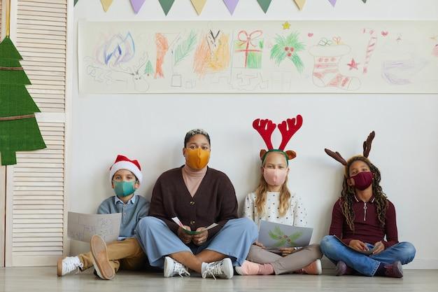 Pełnej Długości Portret Nauczycielki W Masce Siedzącej Na Podłodze Z Wieloetniczną Grupą Dzieci Trzymających Zdjęcia Podczas Zajęć Plastycznych W Boże Narodzenie, Skopiuj Miejsce Premium Zdjęcia