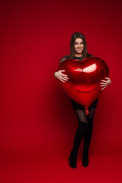 Pełnej Długości Portret Wesoła Brunetka Dziewczyna W Sukience I Butach Obejmujących Czerwony Balon W Kształcie Serca Na Czerwonym Tle. Koncepcja świętego Walentego. Darmowe Zdjęcia