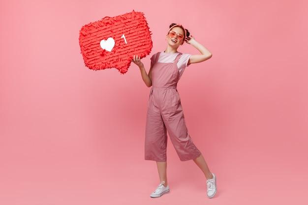 Pełnometrażowy Portret Aktywnej Kobiety W Różowym Stroju I Okularach Przeciwsłonecznych, Trzymając Jak Znak I Skaczący Na Na Białym Tle. Darmowe Zdjęcia