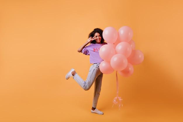 Pełnometrażowy Portret Inspirowanej Afrykańskiej Dziewczyny Stojącej Na Jednej Nodze Z Balonami. Wesoła, ładna Pani świętująca Urodziny. Darmowe Zdjęcia