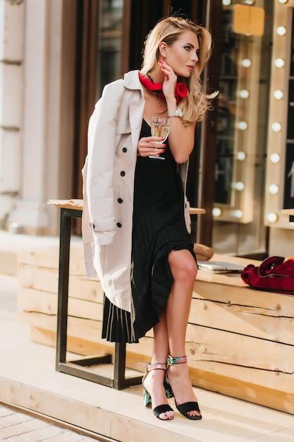 Pełnometrażowy Portret ładnej Blondynki Kobiety Siedzącej Obok Restauracji Przy Lampce Wina I Cieszącej Się Dobrą Pogodą. Odkryty Zdjęcie Dziewczyny W Czarnej Sukni, Picia Samego Szampana. Darmowe Zdjęcia