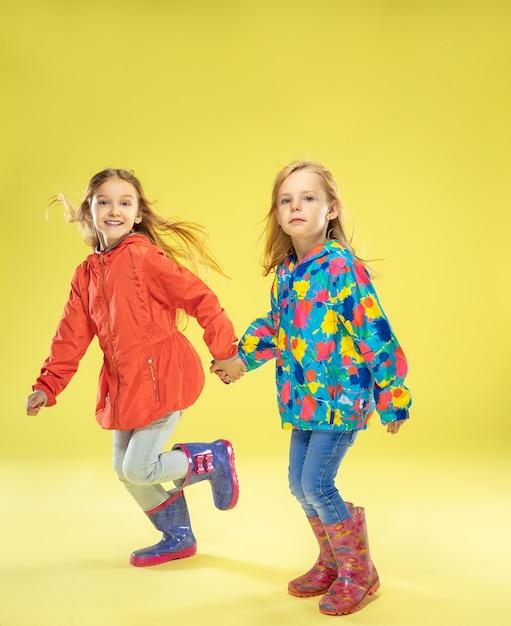 Pełnometrażowy Portret Modnych Dziewczyn W Płaszczu Przeciwdeszczowym Trzymających Się Za Ręce, Biegających I Bawiących Się Na żółtej ścianie Studia Darmowe Zdjęcia