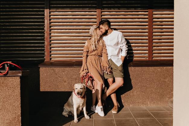 Pełnometrażowy Portret Para Całuje Na Podłoże Drewniane. Dziewczyna W Sukience W Kropki I Jej Modny Brodaty Facet Z Psem. Darmowe Zdjęcia