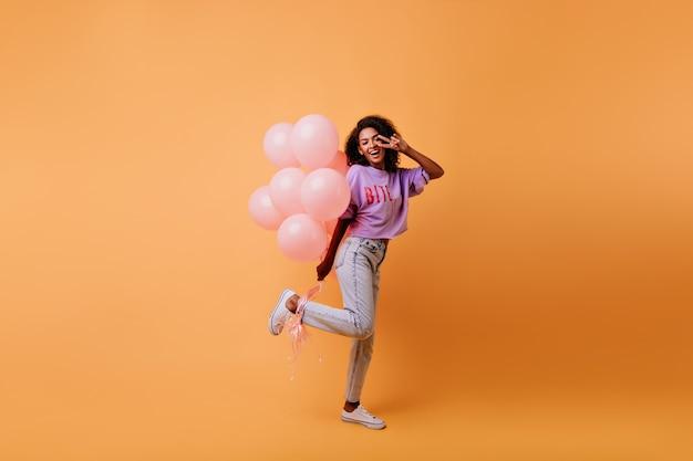 Pełnometrażowy Portret Wyrafinowanej Afrykańskiej Kobiety Przygotowującej Się Do Wydarzenia. Marzycielska Urodzinowa Dziewczyna Tańczy Z Balonami. Darmowe Zdjęcia
